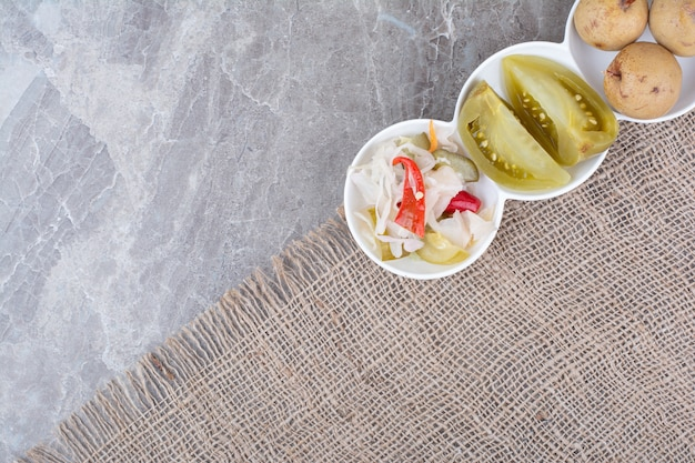Vários legumes e frutas em conserva em tigelas com toalha de mesa.