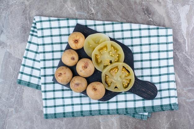 Vários legumes e frutas em conserva no quadro escuro.