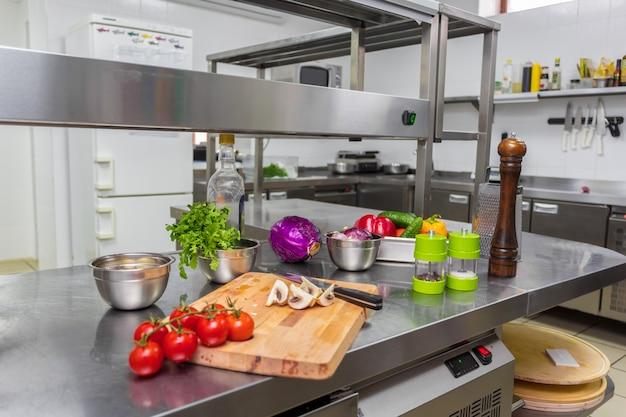 Vários legumes e utensílios de cozinha em uma mesa de cozinha em um restaurante