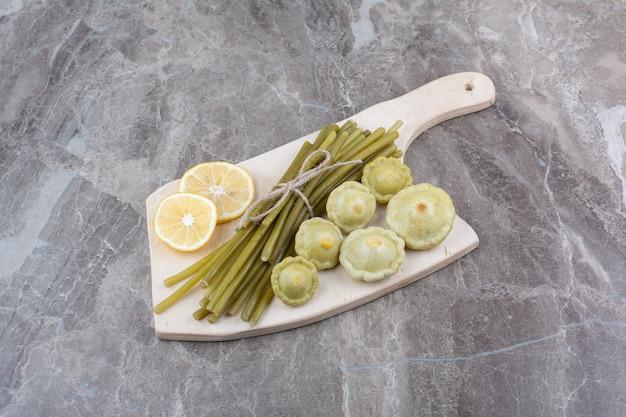 Vários legumes em conserva na placa de madeira.