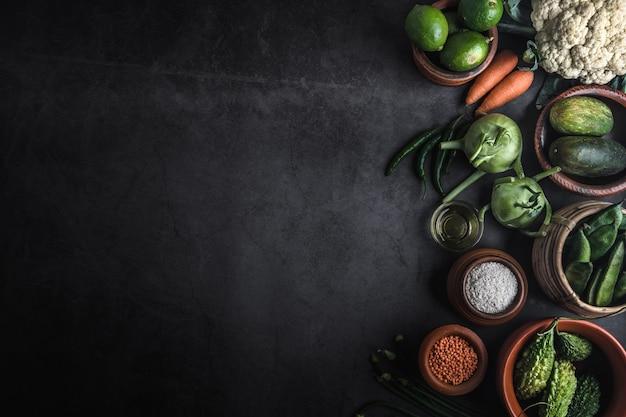 Vários legumes em uma mesa preta com espaço para uma mensagem