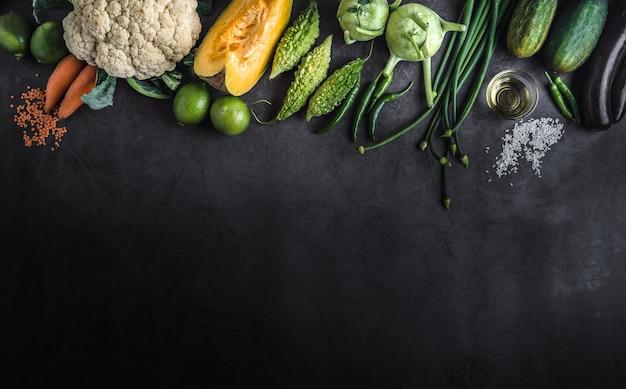 Vários legumes em uma mesa vazia preta com espaço para uma mensagem