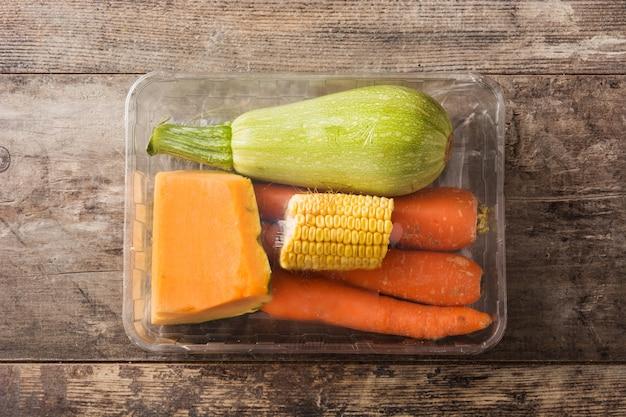 Vários legumes embalados em plástico na mesa de madeira