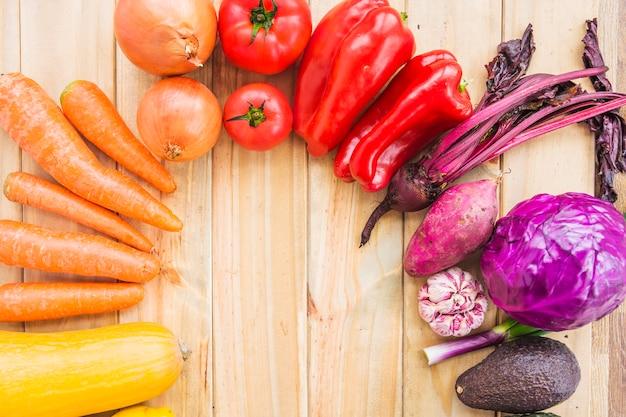 Vários legumes frescos coloridos no cenário de madeira