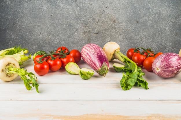 Vários legumes frescos dispostos na mesa de madeira
