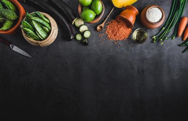 Vários legumes frescos em uma mesa vazia preta com espaço para uma mensagem