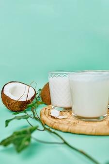 Vários leites e ingredientes vegetais veganos, leite não lácteo, tipos alternativos de leites veganos em copos sobre um fundo azul com espaço de cópia