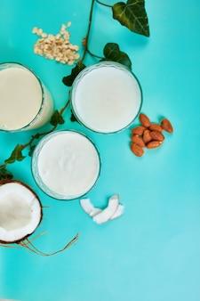 Vários leites e ingredientes vegetais veganos, leite não lácteo, tipos alternativos de leites veganos em copos sobre um fundo azul, disposição plana, vista superior com espaço de cópia