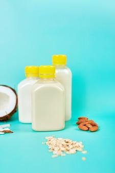 Vários leites e ingredientes vegetais veganos, leite não lácteo, tipos alternativos de leites veganos em garrafa em um fundo azul com espaço de cópia
