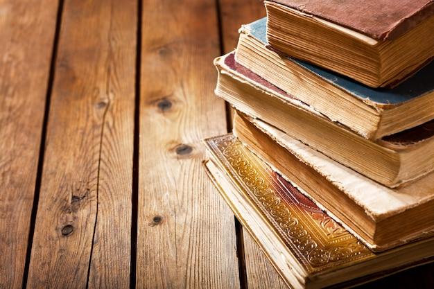 Vários livros antigos em uma mesa de madeira