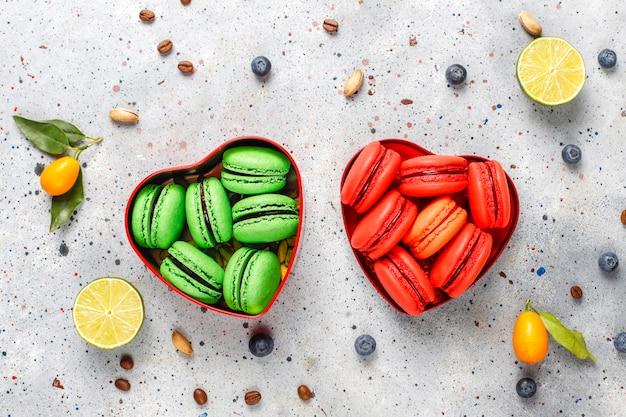 Vários macaroons com pistache, frutas, bagas, grãos de café.
