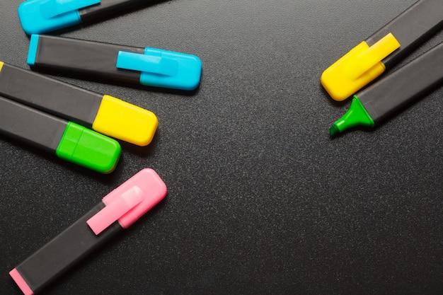 Vários marcadores coloridos na mesa preta close-up