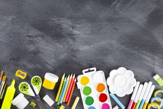 Vários materiais escolares e de pintura em fundo preto. de volta ao conceito de escola. vista do topo. copie o espaço