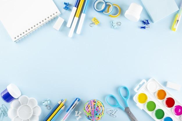 Vários materiais escolares e de pintura sobre fundo azul. de volta ao conceito de escola. vista do topo. copie o espaço