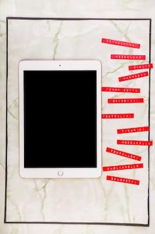 Vários menus ao lado de tablet digital com tela preta em branco