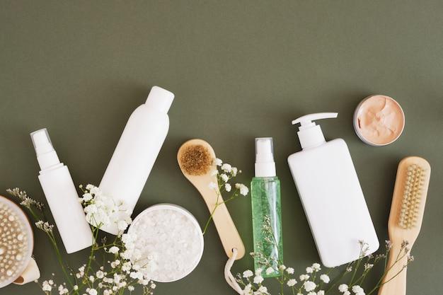 Vários modelos de garrafas em branco e potes para cosméticos em fundo verde escuro, escovas de madeira para massagens e cuidados com o corpo