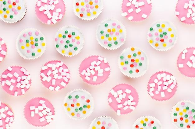 Vários muffins coloridos bem decorados em um fundo branco, vista superior.