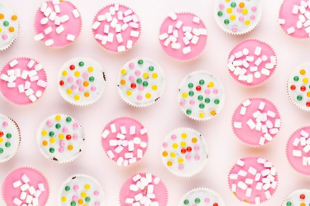 Vários muffins coloridos bem decorados em um fundo branco