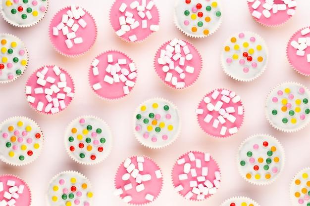 Vários muffins coloridos bem decorados em uma mesa branca
