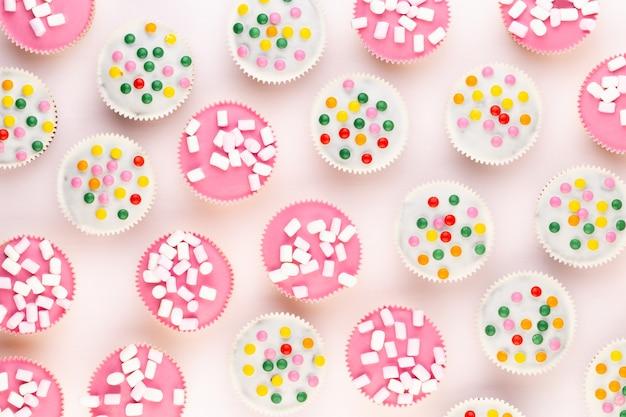 Vários muffins coloridos bem decorados em uma superfície branca, vista superior.