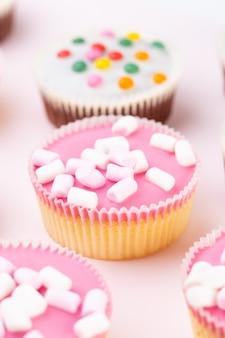 Vários muffins coloridos bem decorados em uma superfície rosa, vista superior.