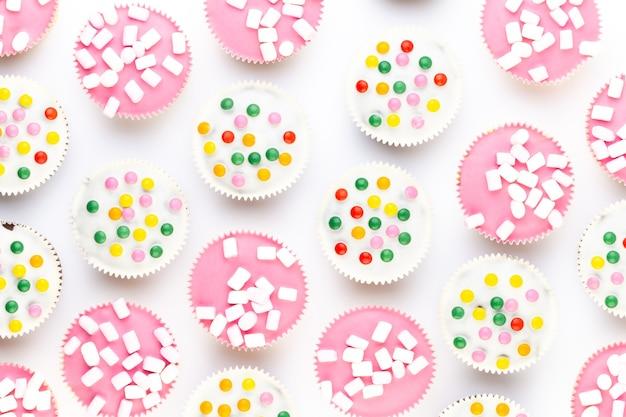 Vários muffins coloridos bem decorados, vista de cima.
