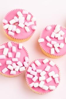 Vários muffins coloridos bem decorados, vista superior.