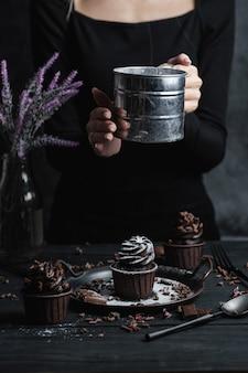 Vários muffins ou cupcakes com creme em forma de chocolate na mesa preta. a mão de uma mulher esmigalha o açúcar de confeiteiro em um bolo.
