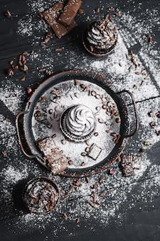 Vários muffins ou cupcakes com creme em forma de chocolate na mesa preta. açúcar em pó é espalhado sobre os bolos.