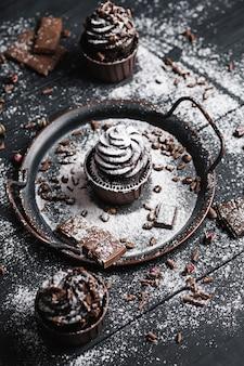 Vários muffins ou cupcakes com creme em forma de chocolate na mesa preta. o açúcar em pó é espalhado sobre os bolos.
