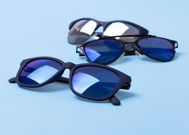 Vários óculos de sol elegantes na mesa criativa azul
