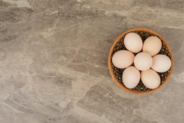 Vários ovos brancos em uma cesta de vime