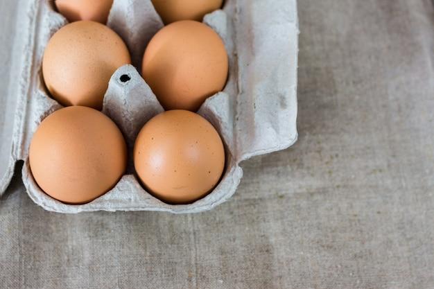Vários ovos em uma caixa de papelão no fundo cinza