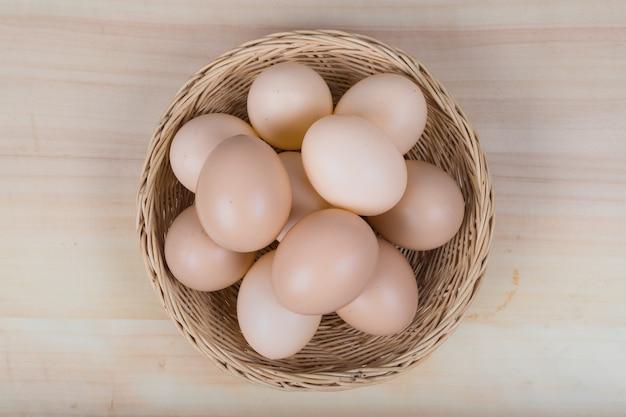 Vários ovos foram colocados em uma cesta de madeira sobre uma mesa de madeira.