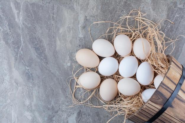 Vários ovos frescos de galinha no feno no fundo de mármore. foto de alta qualidade Foto gratuita
