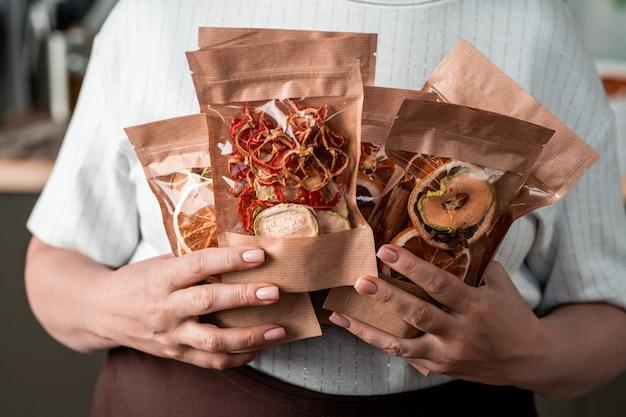 Vários pacotes de papel com frutas secas caseiras nas mãos da dona de casa contemporânea segurando-os pelo peito