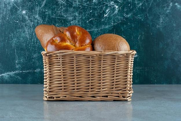 Vários pães e bolos em uma cesta de madeira.