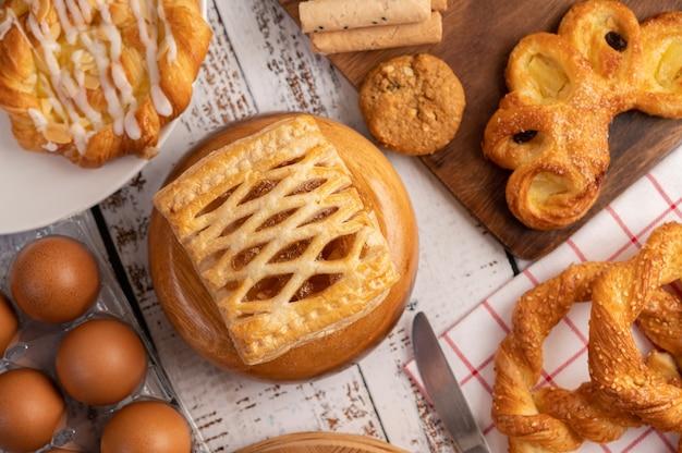 Vários pães e ovos em pano branco vermelho.