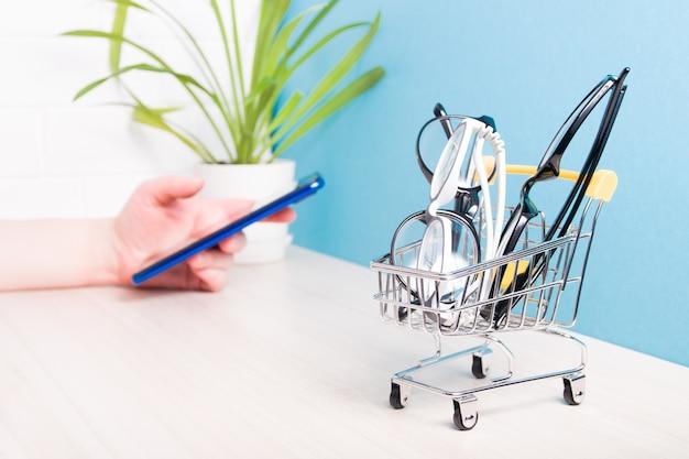 Vários pares de óculos diferentes para correção da visão em um pequeno carrinho de compras sobre a mesa