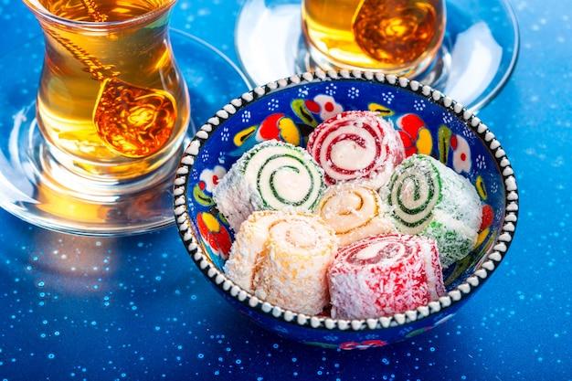 Vários pedaços de lokum de delícias turcas e chá preto