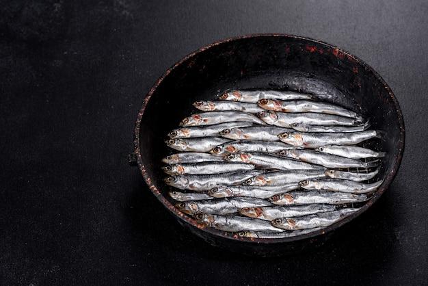 Vários peixes salgaram anchovas em uma mesa de concreto escura. conceito de peixinho
