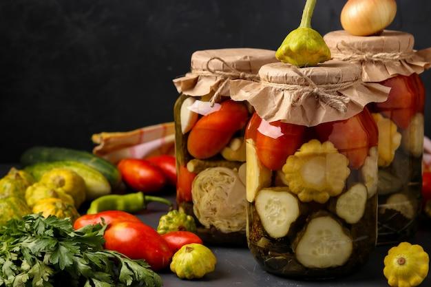 Vários pepinos em conserva, patissons e tomates em potes em fundo escuro, orientação horizontal, espaço de cópia, close-up