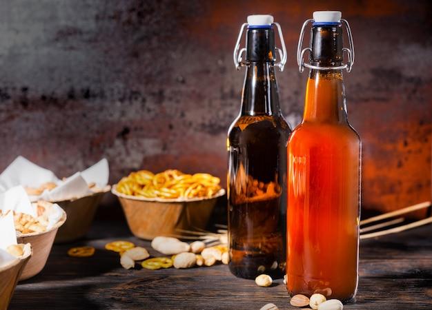Vários petiscos de cerveja em pratos como pistache, pretzels pequenos e amendoim perto de duas garrafas de cerveja filtrada e não filtrada na mesa de madeira escura. conceito de alimentos e bebidas