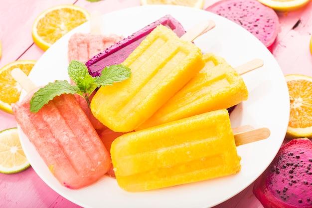 Vários picolés de frutas frescas colocados no fundo da placa de madeira