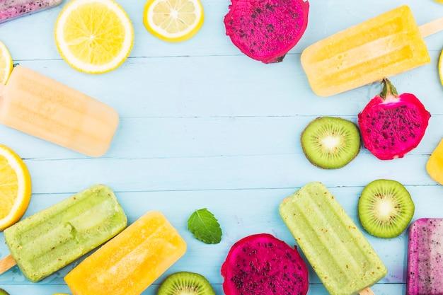 Vários picolés de frutas são colocados no fundo da placa de madeira azul, picolés de kiwi, picolés de laranja, picolés de fruta do dragão, picolé de melão