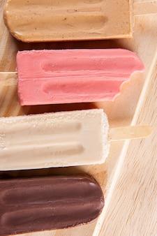 Vários picolés são colocados no fundo da placa de madeira. sabor caramelo, morango, baunilha e chocolate. vista do topo