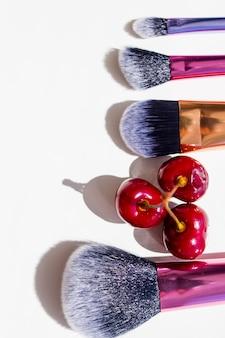 Vários pincéis de maquiagem e cerejas naturais