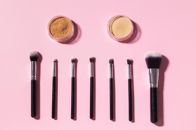 Vários pincéis de maquiagem e pó mineral facial em fundo rosa com cosméticos de vista superior do espaço de cópia