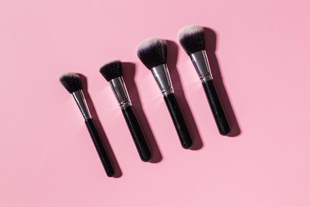 Vários pincéis de maquiagem em cosméticos de vista superior de fundo rosa e conceito de beleza