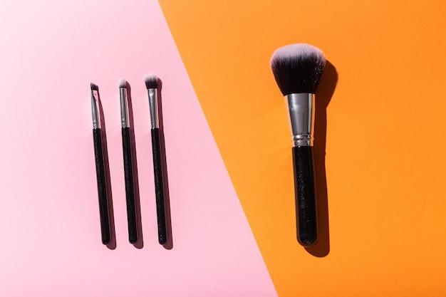Vários pincéis de maquiagem em cosméticos de vista superior de fundo rosa e laranja e conceito de beleza